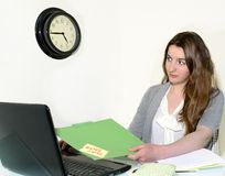 Business Woman Under Time Pressure. Young businesswoman is out of time to  finish her days work Stock Photo