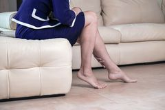 Business woman touching feet with hand. Cropped side view portrait bottom view of woman`s legs and black high heels shoes. Lady stock image
