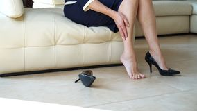 Business Woman Touching Feet With Hand. Cropped Side View Portrait Bottom View Of Woman`s Legs And Black High Heels Shoes. Lady Royalty Free Stock Photography
