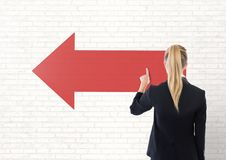 Business woman touching a red arrow against white wall Royalty Free Stock Photos
