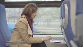 Business woman on the train running on the tablet. Raw video stock video