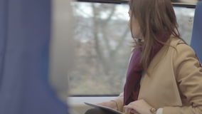 Business woman on train running on tablet. Business woman on the train running on tablet, raw video stock footage
