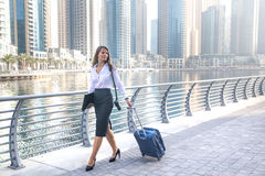 Business woman in transit with a suitcase. Professional business woman in transit with a suitcase Royalty Free Stock Photo