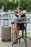 Business woman with travel suitcase reads newspaper at cafe Royalty Free Stock Photo