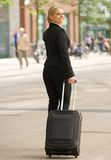 Business woman traveling with suitcase in the city. Portrait of a business woman traveling with suitcase in the city Royalty Free Stock Photography