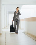 Business woman in trip walking with wheel bag Royalty Free Stock Photo