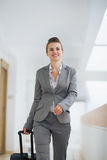 Business woman in trip walking with wheel bag Royalty Free Stock Photography