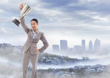 Business woman with trophy on misty mountain peak against skyline stock photo
