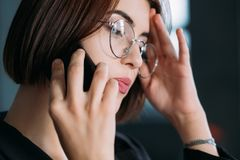 Business woman troubleshooting conversation phone. Business woman portrait. Attractive young female talking on phone. Serious troubleshooting conversation stock photography
