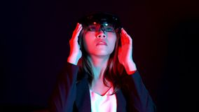 Business woman try vr glasses hololens in the dark room | Portrait of young asian girl experience ar communication | Future. Technology concept stock footage