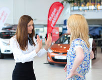 Business woman trying to calm down dissatisfied customer woman. Business women trying to calm down dissatisfied customer women in car service Stock Photo