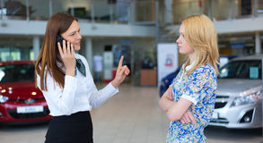 Business woman trying to calm down dissatisfied customer woman. Business women trying to calm down dissatisfied customer women in car service. Selective focus Stock Photos
