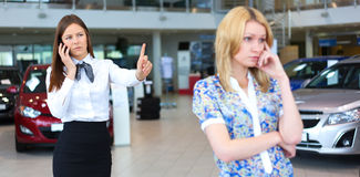 Business woman trying to calm down dissatisfied customer woman. Business women trying to calm down dissatisfied customer women in car service. Selective focus Royalty Free Stock Photography