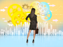 Business woman turned back looks at the city and Royalty Free Stock Photography