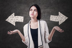 Business woman with two arrows. Confused business woman with two arrows on blackboard Stock Photos