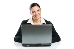 Business woman typing on laptop. Young business woman typing on her laptop isolated on white background Stock Image