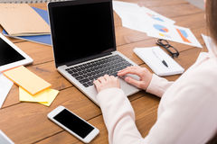 Business woman typing on laptop with blank screen. Copy space Royalty Free Stock Photography