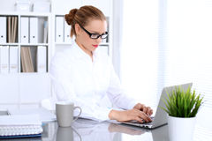 Business woman is typing on laptop computer. Bookkeeper or female financial inspector  making report, calculating or checking balance Stock Images