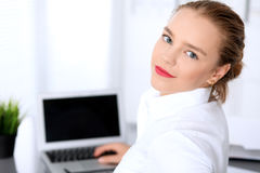 Business woman is typing on laptop computer. Bookkeeper or female financial inspector  making report, calculating or checking balance Stock Image