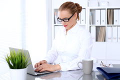 Business woman is typing on laptop computer. Bookkeeper or female financial inspector  making report, calculating or checking balance Royalty Free Stock Photo
