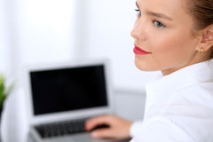 Business woman is typing on laptop computer. Bookkeeper or female financial inspector  making report, calculating or checking balance Stock Photo