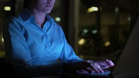Business woman typing laptop at night in office, lighted by computer screen. Stock footage stock footage