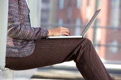 Business woman typing on laptop outside. Side portrait of a business woman typing on laptop outside Royalty Free Stock Images