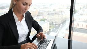 Business woman typing on laptop. Sitting by the window in office stock video footage