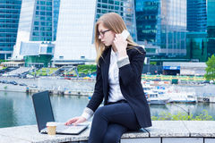 Business woman typing on laptop and talking on the phone on the background of skyscrapers Stock Images
