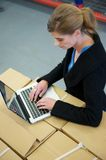 Business woman typing on laptop in warehouse. Portrait of a business woman typing on laptop in warehouse Stock Photos
