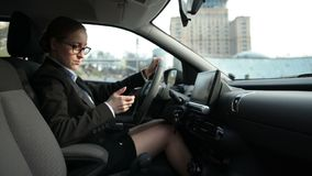 Business woman typing message on phone in car. Elegant female driver in business outfit sitting behind the steering wheel and typing message on smart phone stock video footage