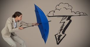 Business woman with umbrella blocking storm graphic against brown background stock photo