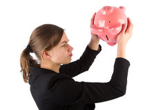 Business woman is unable to get money out of piggy bank Stock Photo