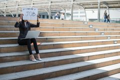 Business woman unemployed from company sitting on the staircase and holding poster with text is looking for job. Concept of unemployment problem royalty free stock photo
