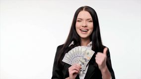 Business woman with us dollar money. Closeup of young business woman with us dollar banknotes in hand  thinking of how to spent them and gesturing thumb up stock video
