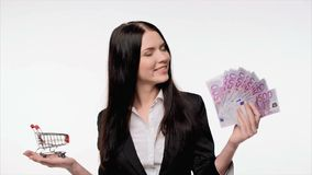 Business woman with us dollar money. Closeup of young business woman with euro banknotes in one hand  and small empty shopping cart in another, choosing stock footage