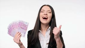 Business woman with us dollar money. Closeup of young business woman with euro cash banknotes in hand enjoying success gesturing thumb up, ok signs stock footage