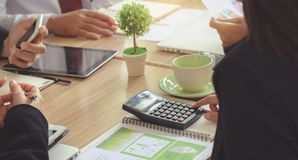 Business woman Use a calculator to calculate. Analysis of figure. S during the conference. Focus on calculator stock images
