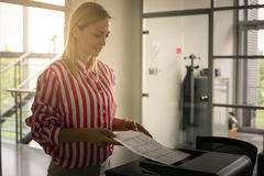 Business woman uses copier. Businesswoman using photocopier in office Royalty Free Stock Photography