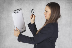 Business woman uses a magnifying glass to read the agreement. Businesswoman uses a magnifying glass to read the agreement Royalty Free Stock Images