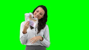 A business woman uses money as a fan stock footage