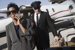 Business Woman Using Cellphone At Airfield. Business women on a call while driver keeping luggage in car at airfield Stock Image