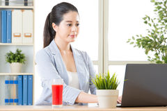 Business woman using computer and drinking fresh watermelon juic Royalty Free Stock Photos