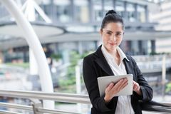 Business woman using digital tablet computer outside office. happy young beautiful girl working on social media outdoor over royalty free stock images