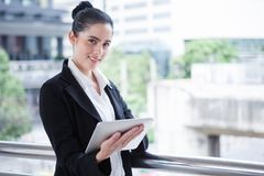 Business woman using digital tablet computer outside office. happy young beautiful girl working on social media outdoor over stock image