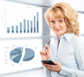 Business woman using her smartphone. On the background graphics and charts Stock Photography