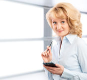 Business woman using her smartphone. On the background graphics and charts Stock Photo