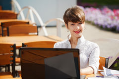 Happy businesswoman with laptop at sidewalk cafe Royalty Free Stock Image