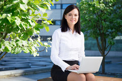 Business woman using laptop in city park Royalty Free Stock Photo