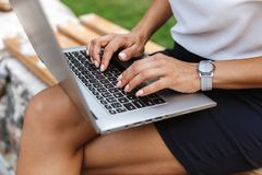 Business woman using laptop computer outdoors. Image of a beautiful business woman using laptop computer outdoors royalty free stock image